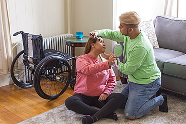 Brother applying make-up on her sister's face, who has Spinal Cord Injury