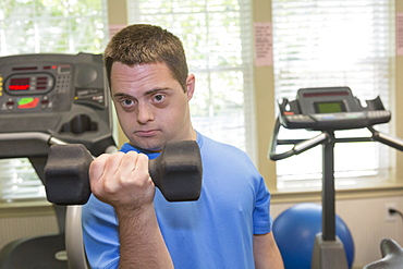 Man with Down Syndrome exercising in a gym with dumbbell