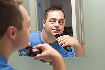 Man with Down Syndrome shaving in bathroom