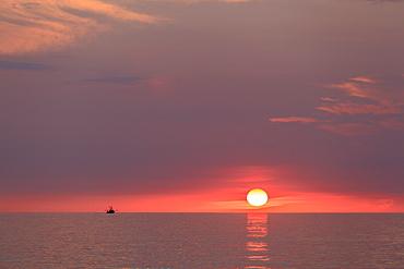 Sunrise over ocean on Block Island with fishing trawler, Rhode Island, USA