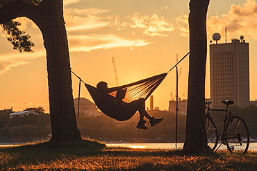 A young man sits reading in a hammock between two trees at the water's edge at sunset with a bicycle leaning against the tree and buildings across the water