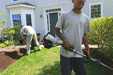 Landscapers working in a garden, one doing mulching and one doing edging with a power edger