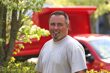 Landscaper in a garden with his truck in the background