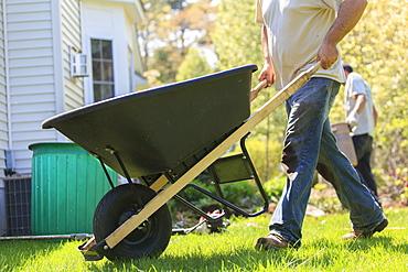 Landscaper moving wheelbarrow around a house