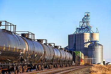 Tank cars on a train approaching a grain storage facility; Alberta, Canada