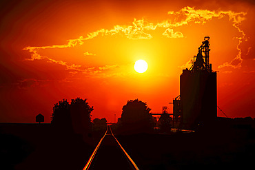 A grain storage facility at sunset with a bright yellow sun in the glowing red sky; Alberta, Canada