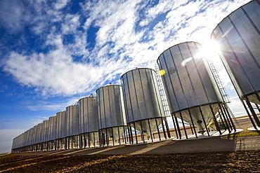 Silver metal grain storage bins in a row against a blue sky with cloud; Alberta, Canada