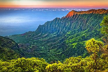 View of Na Pali Coast and Kalalau Valley from Pu'u O Kila Lookout, sunset glow on the rugged cliff, Koke'e State Park; Kauai, Hawaii, United States of America