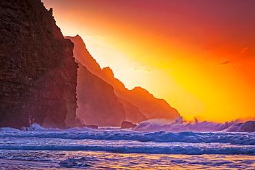 Bright orange sunset behind the rugged mountains along the Na Pali Coast, Kalalau Beach, Na Pali Coast State Park; Kauai, Hawaii, United States of America