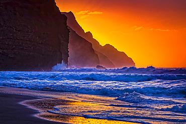 Sunset behind the rugged mountains along the Na Pali Coast, Kalalau Beach, Na Pali Coast State Park; Kauai, Hawaii, United States of America