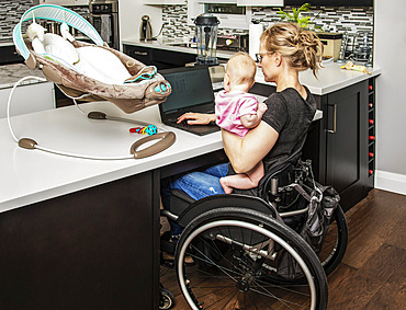 A young mom with a spinal cord injury looks after her newborn baby while working on her computer in the kitchen; Edmonton, Alberta, Canada