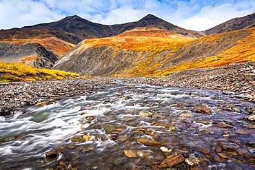 Kuyuktuvuk Creek and Brooks Mountains in fall colours. Gates of the Arctic National Park and Preserve, Arctic Alaska in autumn; Alaska, United States of America