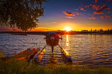 Sunset behind a float plane at Lake Hood Seaplane Base, South-central Alaska in summertime; Anchorage, Alaska, United States of America