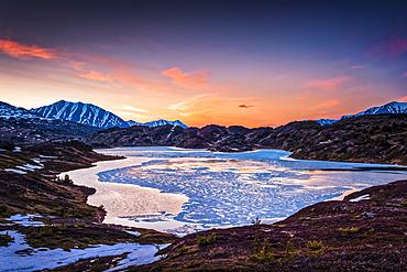 Half frozen Lost Lake at evening, Chugach Mountains in the background. Chugach National Forest, Kenai Peninsula, South-central Alaska in springtime; Seward, Alaska, United States of America