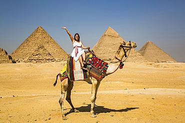 Female tourist waving while sitting on a camel, Giza Pyramid Complex, UNESCO World Heritage Site; Giza, Egypt