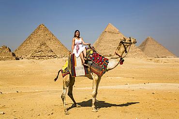 Female tourist on a camel, Giza Pyramid Complex, UNESCO World Heritage Site; Giza, Egypt