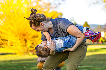 A mother plays with her toddler daughter in a park with autumn colours; North Vancouver, British Columbia, Canada