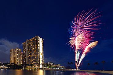 Condominiums and fireworkds along the coastline of Waikiki at sunset; Honolulu, Oahu, Hawaii, United States of America