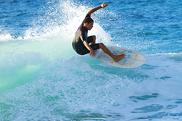 Surfer riding a turquoise wave off the North shore of Oahu; Oahu, Hawaii, United States of America