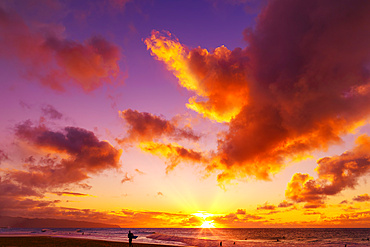 Silhouette of a surfer standing on Kelki Beach at the water's edge with dramatic glowing clouds above at sunset; Oahu, Hawaii, United States of America