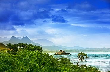 Mist over Kaupo Cove at sunrise, with a pier leading to a house and mountain peaks lining the coastline; Oahu, Hawaii, United States of America