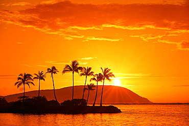 Sunrise at Kahala Beach, Waiʻalae Beach Park, with rays of the sun in a glowing sky reflected in the tranquil water; Oahu, Hawaii, United States of America