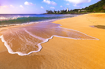 Surf on the golden sand at Waimea Bay Beach Park at sunrise; Oahu, Hawaii, United States of America