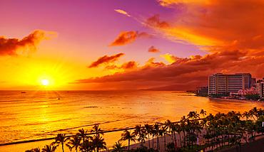 Condominiums and palm trees along the coastline of Waikiki at sunrise; Honolulu, Oahu, Hawaii, United States of America
