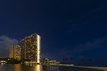 Condominiums along the coastline of Waikiki at sunrise; Honolulu, Oahu, Hawaii, United States of America