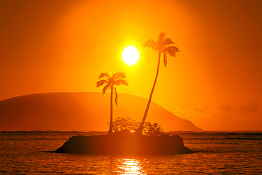 Sunrise at Kahala Beach, Waiʻalae Beach Park, with a flare around the sun in a glowing red sky reflected in the tranquil water; Oahu, Hawaii, United States of America