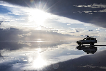 Four-wheel drive and reflection during the wet season (December-February) in Salar de Uyuni, the world's largest salt flat; Potosi Department, Bolivia