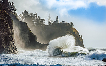 Cape Disappointment Light with large waves crashing in onto the beach below, Cape Disappointment; Washington, United States of America