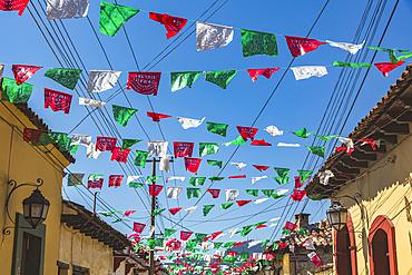 Garlands strung across a street between buildings; San Cristobal de las Casas, Chiapas, Mexico