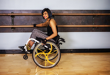 A paraplegic woman popping wheelie in her wheelchair and fooling around in a gymnasium after working out at a fitness facility: Sherwood Park, Alberta, Canada
