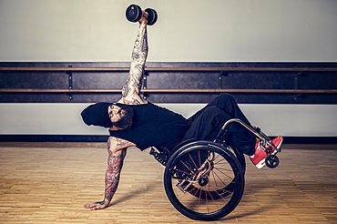 A paraplegic man popping a wheelie in his wheelchair and balancing while lifting a weight in a gymnasium after working out at a fitness facility: Sherwood Park, Alberta, Canada