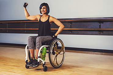 A paraplegic woman taking a break in a gymnasium after working out in a recreational facility: Sherwood Park, Alberta, Canada