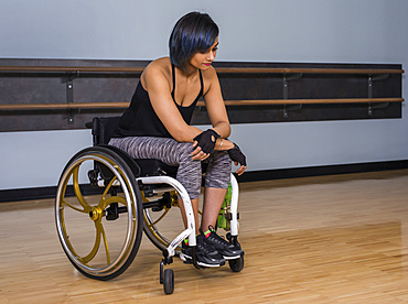 A paraplegic woman looking discouraged while taking a break from working out in a recreational facility: Edmonton, Alberta, Canada