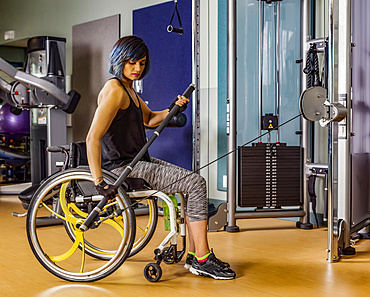 A view from the side of a paraplegic woman working out using a bar connected to a pull down machine in a fitness facility; Sherwood Park, Alberta, Canada