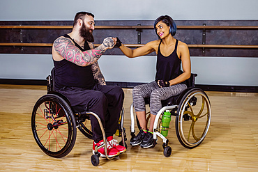 Two paraplegic friends giving each other a fist bump of encouragement after working out at a fitness facility: Sherwood Park, Alberta, Canada