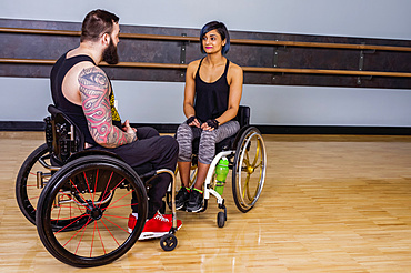 Two paraplegic friends talking together and encouraging each other after working out at a fitness facility: Sherwood Park, Alberta, Canada