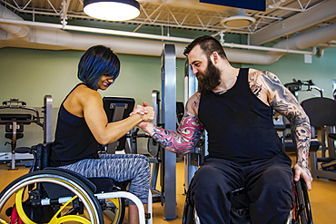 Two paraplegic friends pretending to arm wrestle after working out at a fitness facility: Sherwood Park, Alberta, Canada
