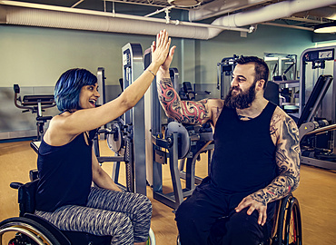 Two paraplegic friends giving each other a high five after working out at a fitness facility: Sherwood Park, Alberta, Canada