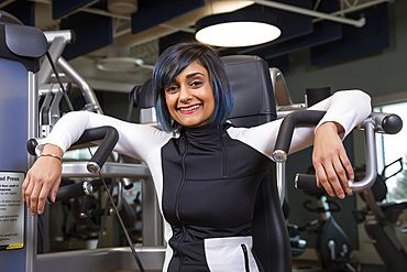 A paraplegic woman posing for the camera after working out using an overhead press in a fitness facility; Sherwood Park, Alberta, Canada