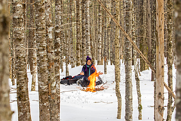 A woman with snowshoes sits on the snow and warms up by a campfire in a forest in wintertime, Gaspesie National Park; Quebec, Canada