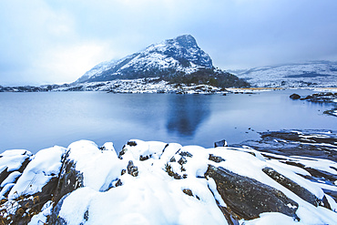 Small mountain surrounded by low clouds by one of the upper lakes in killarney with snow covered rocks in the foreground, Killarney National Park; County Kerry, Ireland