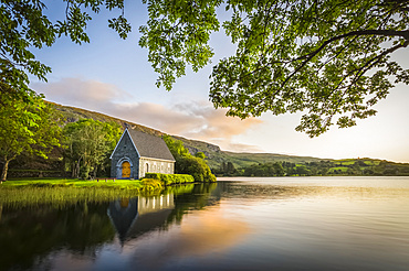 Old chapel of Gougane Barra situated by a lake and framed by green trees at sunrise; Gougane Barra, County Cork, Ireland