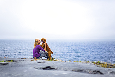 Woman embracing dog on a rocky ground overlooking the sea on a cloudy day; Fanore, County Clare, Ireland