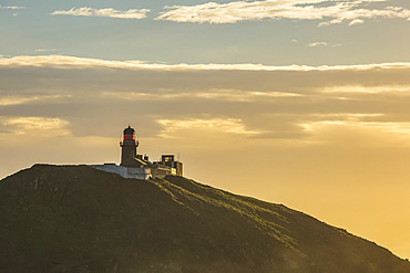 Silhouette of Ballycotton lighthouse being hit with the morning sun; Ballycotton, County Cork, Ireland