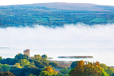 Castlebawn Tower house on the banks of Lough Derg surrounded in fog on an autumn morning; Clare, Ireland