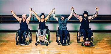 A group of paraplegic friends raising their hands together in victory after a workout in fitness facility: Sherwood Park, Alberta, Canada